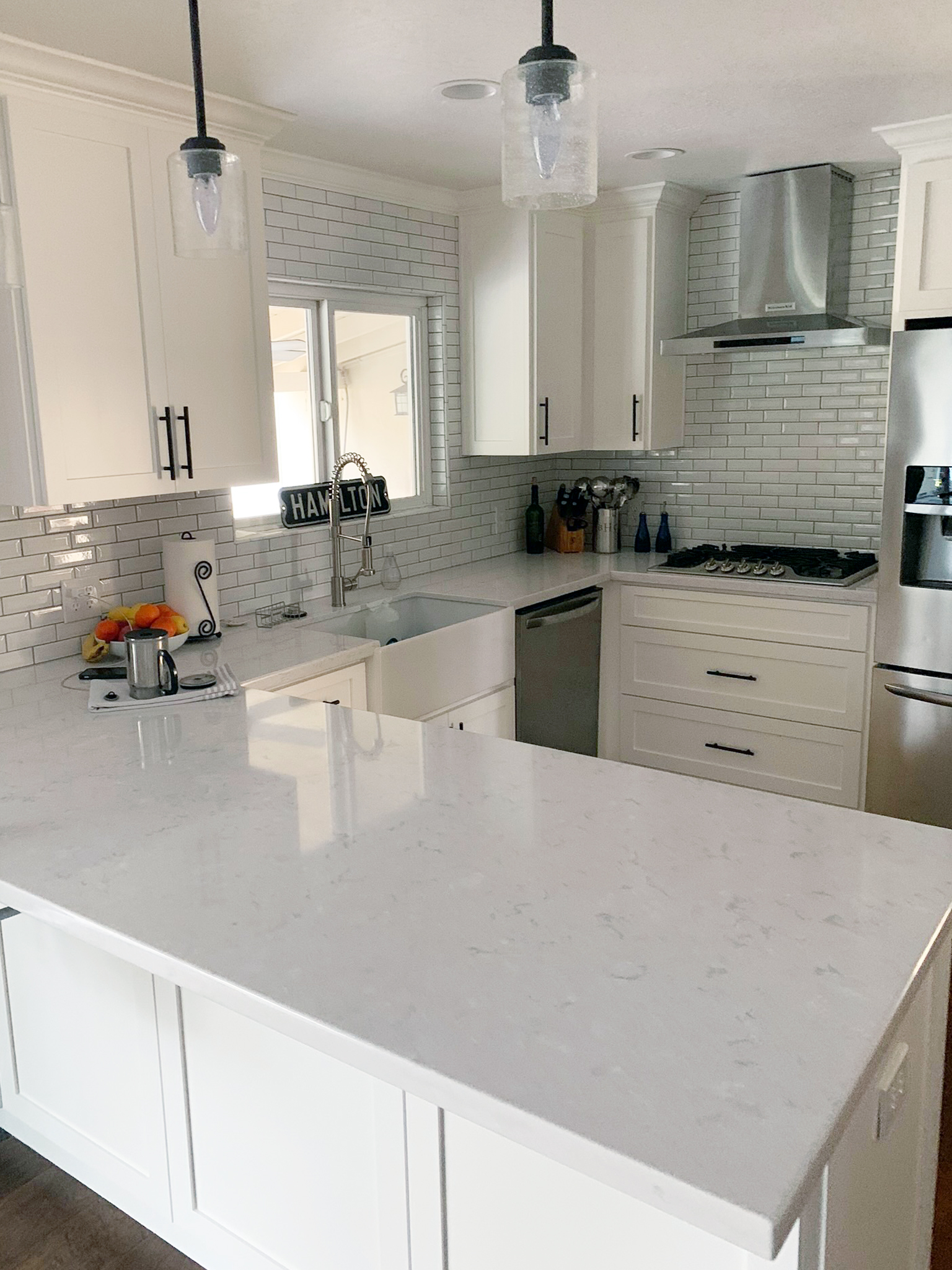 Kitchen remodel with white subway backsplash and white cabinets
