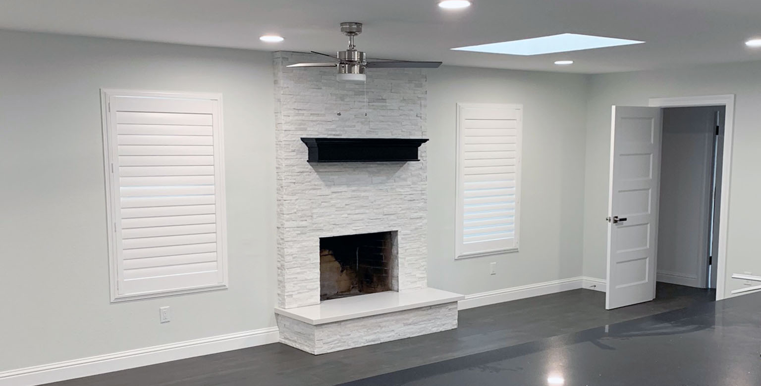 White stone fireplace in a living room remodel.